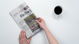 hands holding a folded newspaper with a cup coffee next to it