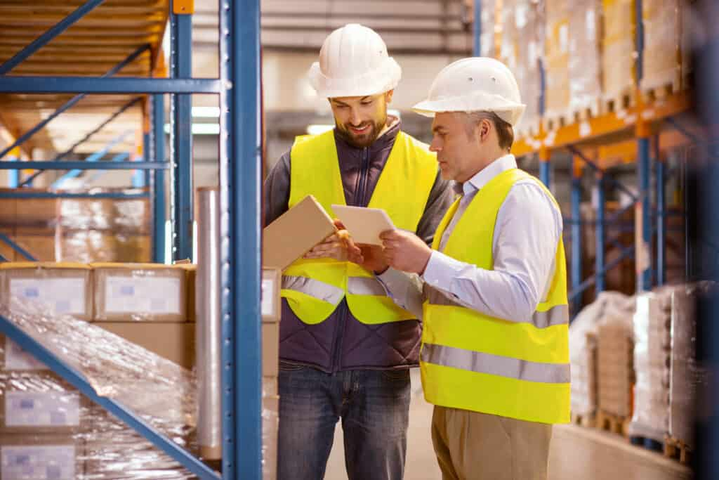 Large scale trade. Delighted nice man holing a box while standing with his colleague in the warehouse to show how important inventory control is.