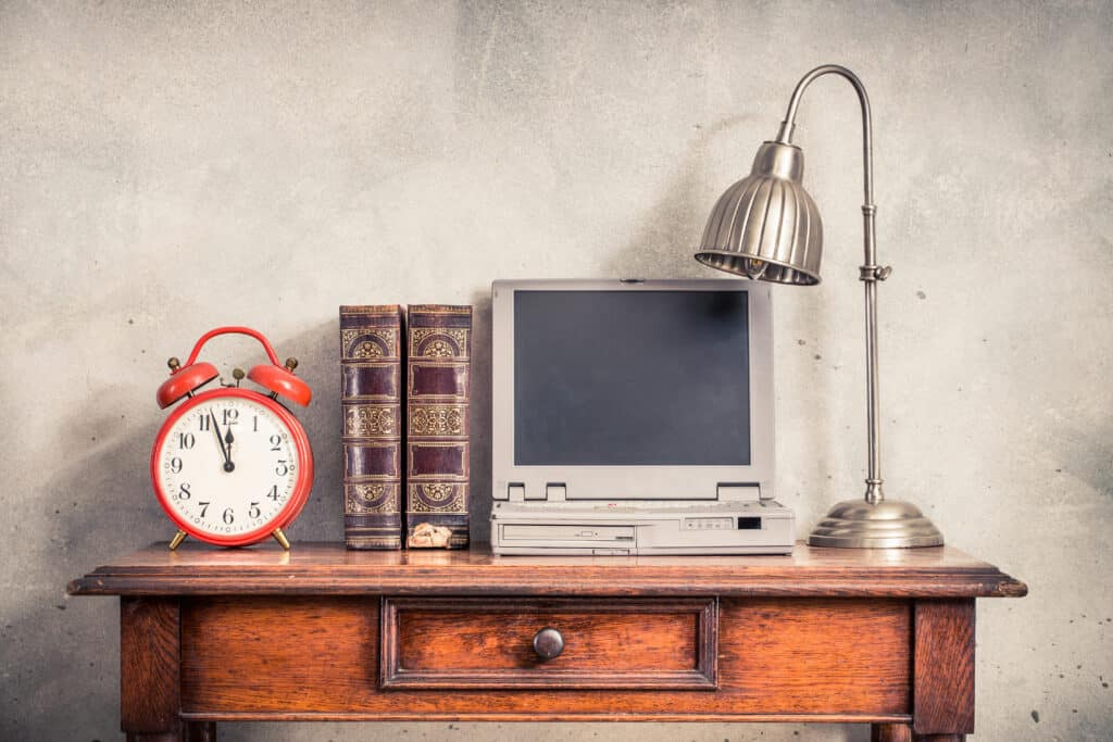 A picture of an old computer and alarm clock.Don't get stuck using outdated software!