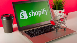 An image of a the Shopify logo on a latptop with inventory management strategies implied.