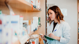 A young female pharmacy worker manually checking her stock. Comparing numbers manually with a medical inventory management system is a good way to ensure proper counts.