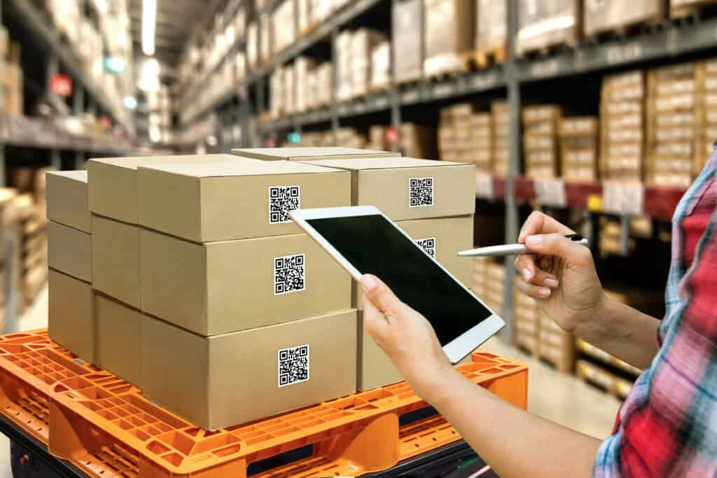 Industrial 4.0 , Augmented reality and smart logistic concept. Hand holding tablet with AR application for check order pick time around the world and supply chain in smart factory background. Using an order management system.