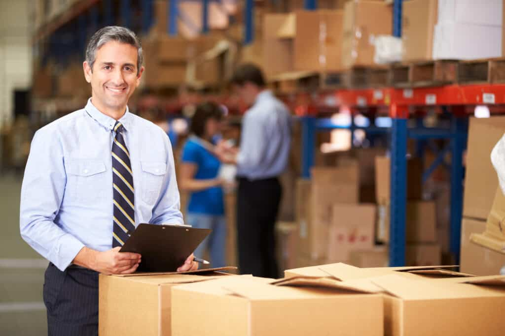 Manager In Warehouse Checking Boxes using an order management system.