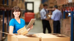 Worker In Warehouse Checking Boxes Using Digital Tablet and an Order Management System